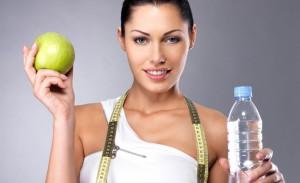 Una giovane donna tiene in mano una mela e una bottiglia d'acqua