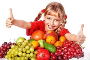 Bambina con un piano pieno di frutta sorride. Pesticidi nei cibi: alimenti europei sicuri il 97%