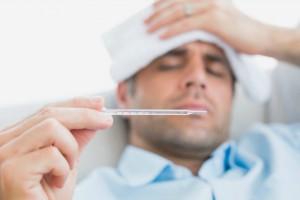 vaccino, un uomo a letto con la febbre