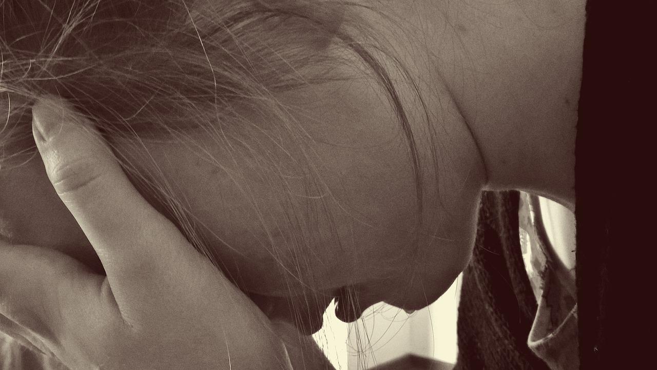 Una ragazza con la testa tra le mani