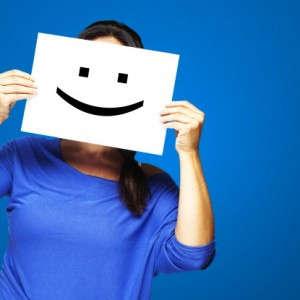 Stress da isolamento, donna mantiene un cartello con un sorriso disegnato