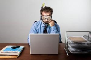 Sindrome da rientro. Uomo in ufficio seduto alla scrivania