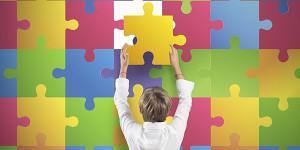 Autismo, un bambino inserisce la tessera di un puzzle