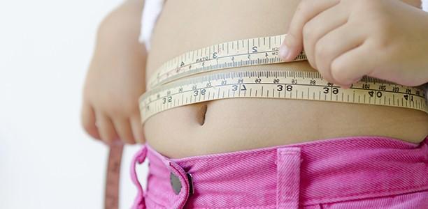 Obesità e fegato grasso, un uomo misura la circonferenza dello stomaco