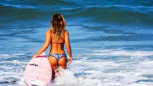 sole e abbronzatura, una donna con un surf