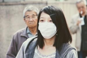 Cina, una donna con la mascherina