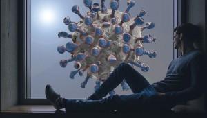 Covid-19: un uomo guarda dalla finestra dove campeggia un immagine del virus che ha scatenato la pandemia