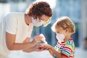 Covid, un ragazzo aiuta un bambino a disinfettare le mani