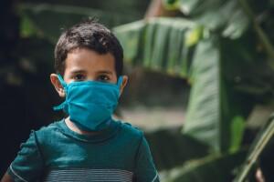 vaccinazione, un bambino indossa la mascherina