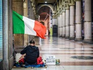 povertà a pasqua. Uomo siede per terra sotto la bandiera italiana