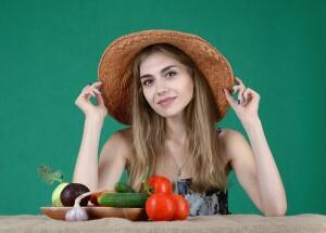 Pomodoro, una donna con un cappello di paglia e della verdura e ortaggi sul tavolo davanti a lei