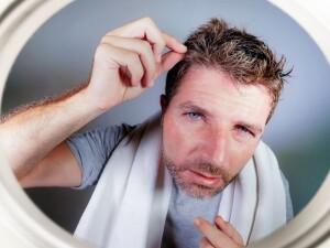 capelli grigi e stress, un uomo si specchia