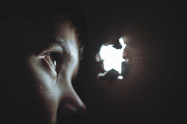 Karim, una foto generica di un bambinno che guarda attraverso un buco in una scatola di cartone