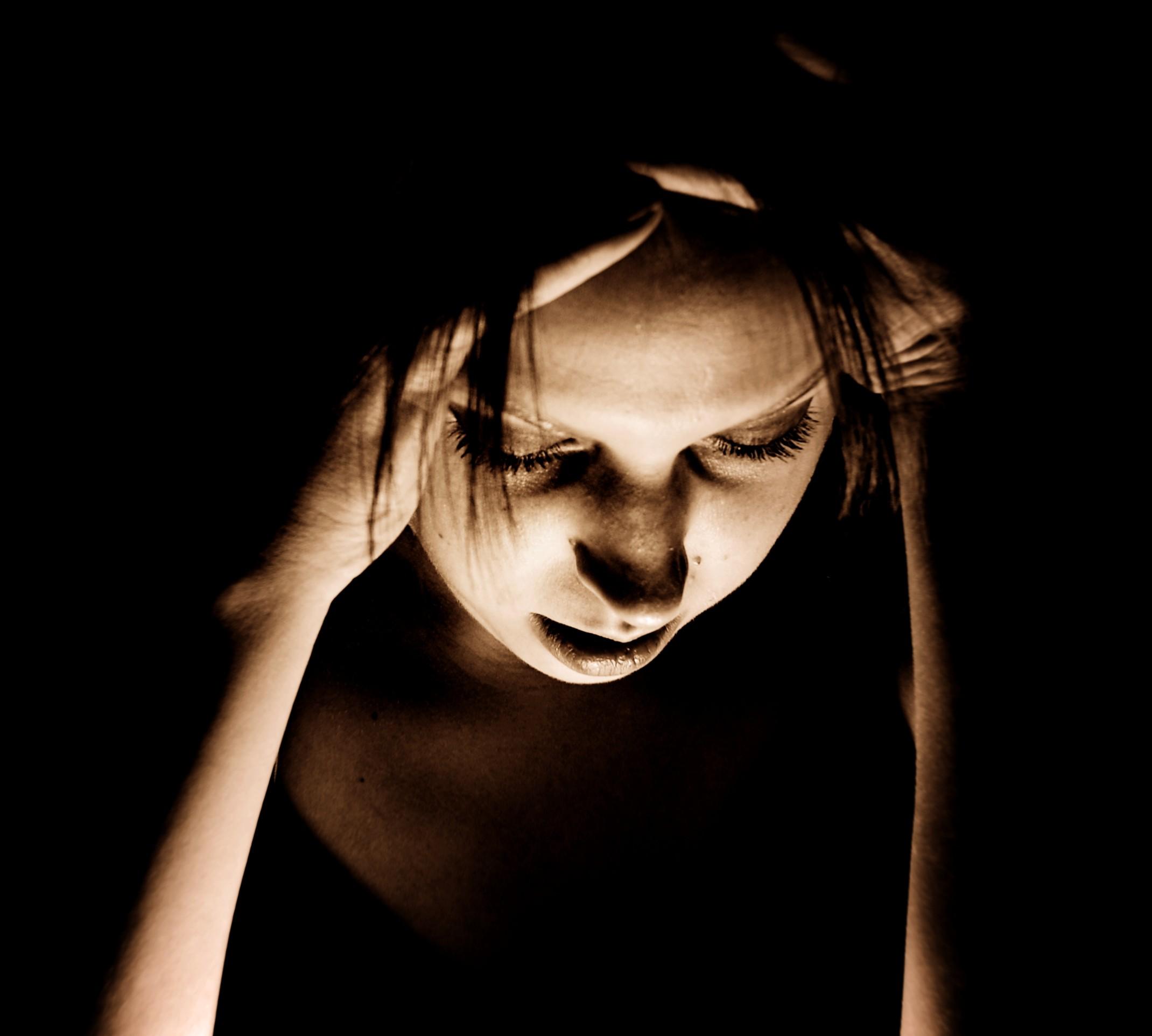 Emicrania, una donna con le mani alla testa